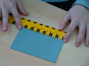 Pupil measuring the length of a rectangle using a special ruller for the blind