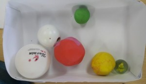 The photograph shows a box with six balls, three of them are the models (large, medium, small) and the other three are identical with the models made from plasticine